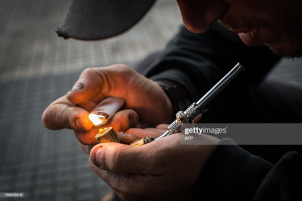 A drug addict lights an improvised pipe in 'Crackolandia', a place where drug addicts gather to smoke crack, in downtown Sao Paulo Brazil on January 11, 2013. AFP PHOTO/Yasuyoshi CHIBA
