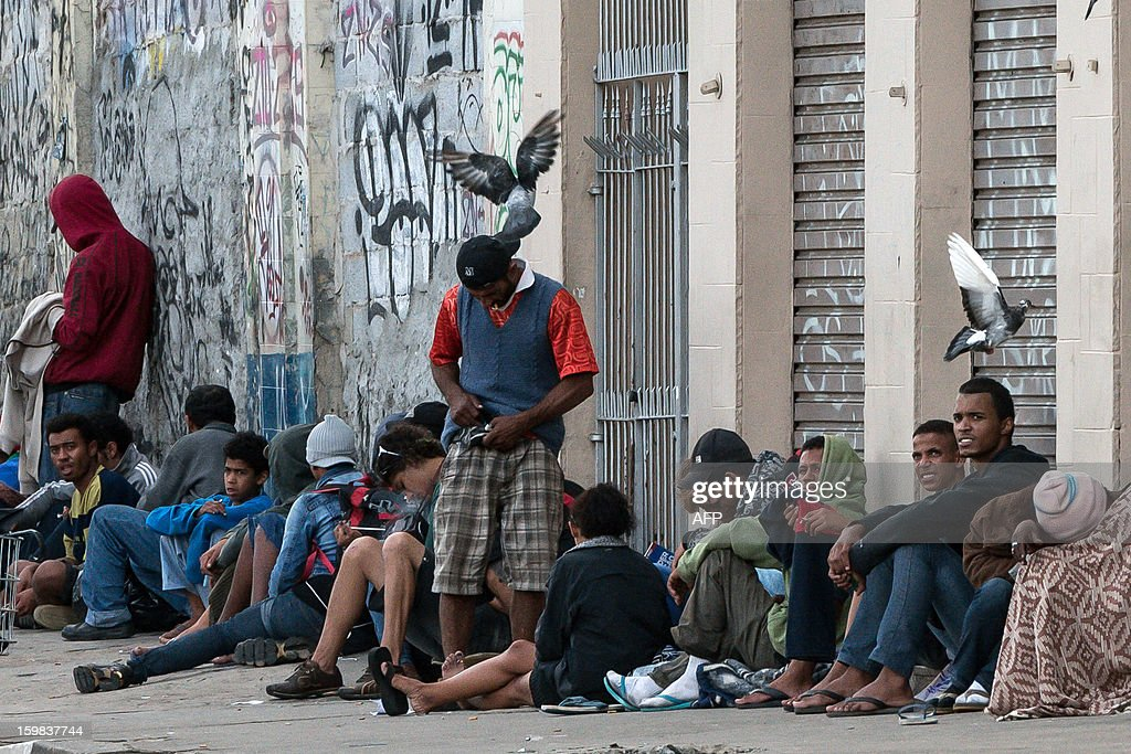 Drug addicts gather together on a sidewalk in 'Crackolandia', a place where they smoke crack, in downtown Sao Paulo, Brazil on January 21, 2013. AFP PHOTO/Yasuyoshi CHIBA