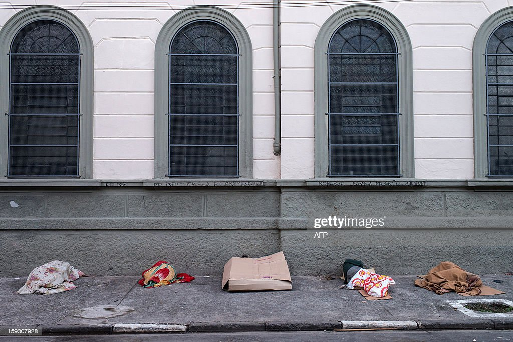 Drug addicts sleep along the sidewalk next to a CathoLic church at so called 'Crackolandia', a place where drug users gathering to smoke crack cocaine, in downtown Sao Paulo, Brazil on January 11, 2013. AFP PHOTO/Yasuyoshi CHIBA