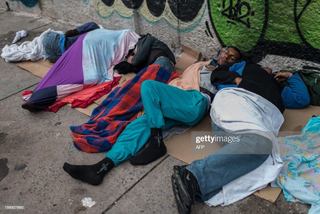 Drug addicts sleeps along the sidewalk at so called 'Crackolandia', a place where drug users gathering to smoke crack cocaine, in downtown Sao Paulo Brazil on January 11, 2013. AFP PHOTO/Yasuyoshi CHIBA