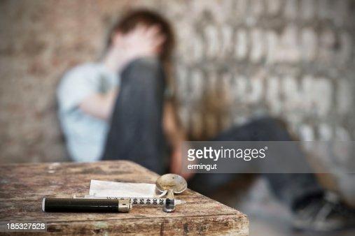 Drug paraphernalia with blurred addict behind