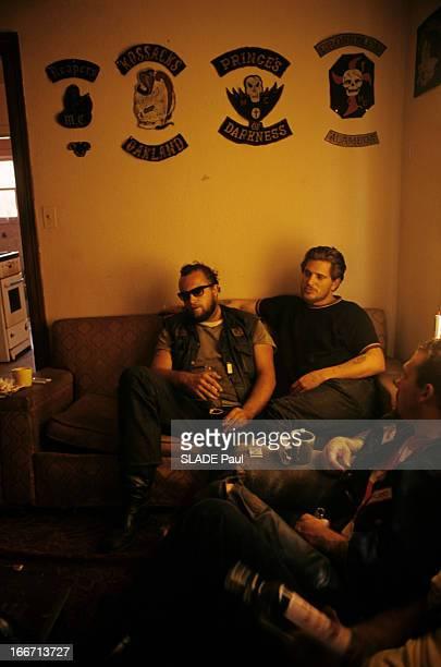 Drugs Lsd Aux EtatsUnis dans une pièce deux motards tatoués assis dans un canapé contre un mur où sont affichés des insignes de clans de motards...
