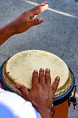Drum player playing atabaque during presentation of afro music on the eve of the Brazilian carnival