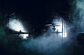 cymbals set and drums in smoke and light of searchlights