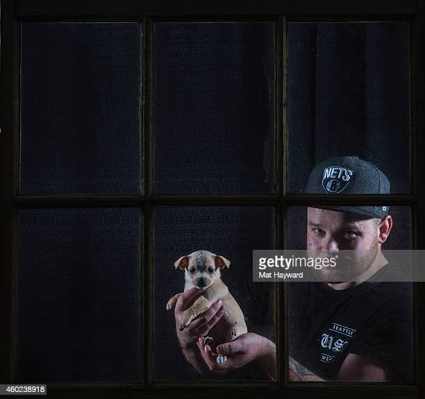 Drummer Ben Thatcher of Royal Blood holds a puppy brought by Motley Zoo Animal Rescue backstage during Deck the Hall Ball hosted by 1077 The End at...
