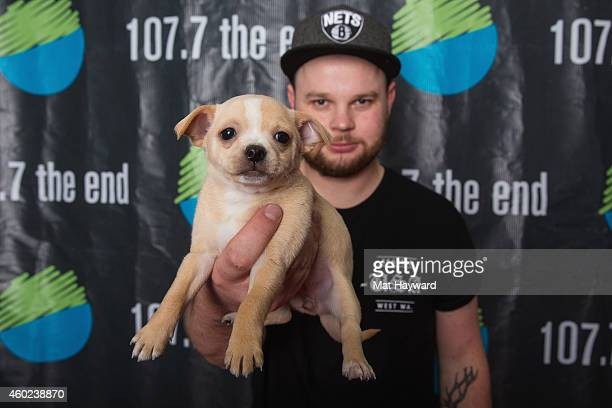 Drummer Ben Thatcher of the band Royal Blood holds a pupppy brought by Motley Zoo Animal Rescue backstage during Deck the Hall Ball hosted by 1077...
