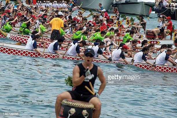 A drummer coaches his team as a Dragon Boat race takes places behind him on June 23 2012 in the Stanley District of Hong Kong The races held every...