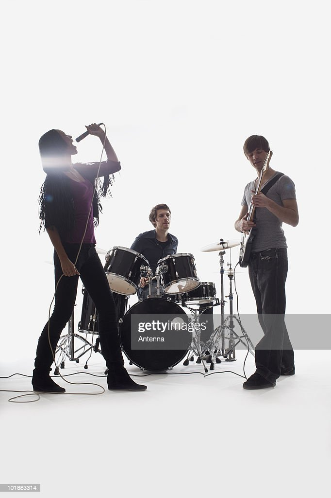 A drummer, guitarist and singer performing, studio shot, white background, back lit