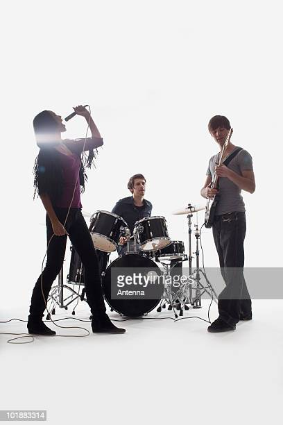 A drummer, guitarist and singer performing, studio shot, white background, back lit