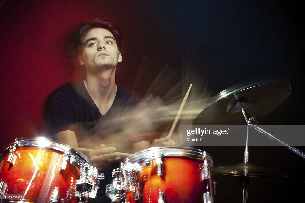 Drummer in motion playing drums : Stock Photo