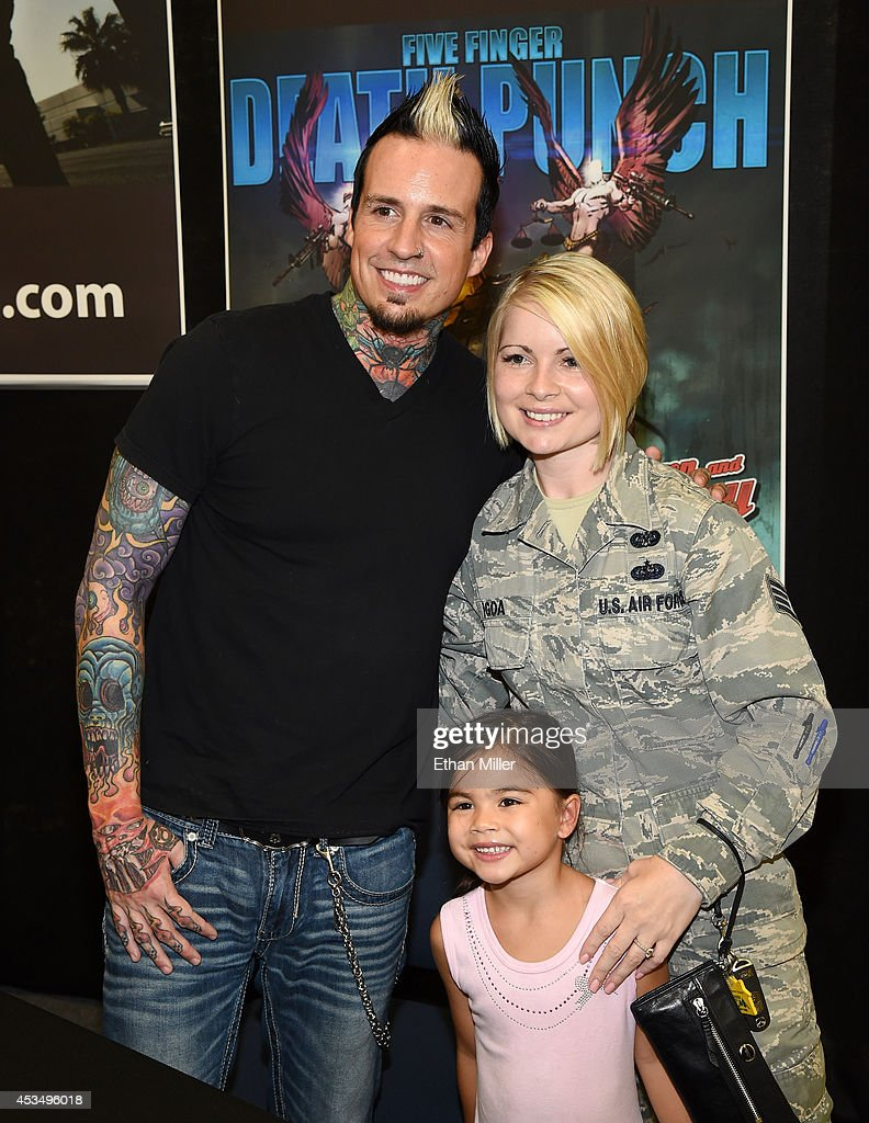 Drummer Jeremy Spencer of Five Finger Death Punch poses for a photo with Staff Sgt. Nicole Igoa and her daughter Kalena Igoa, 6, at Nellis Air Force Base as the band highlights its campaign to raise awareness about veterans suffering from post-traumatic stress disorder (PTSD), in part by launching the video 'Wrong Side of Heaven,' that deals with the subject on August 11, 2014 in Las Vegas, Nevada.