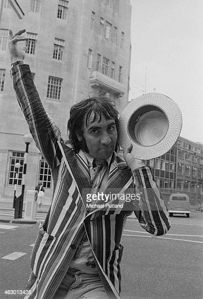 Drummer Keith Moon of The Who posing in a striped blazer and straw boater outside Broadcasting House London 11th July 1973