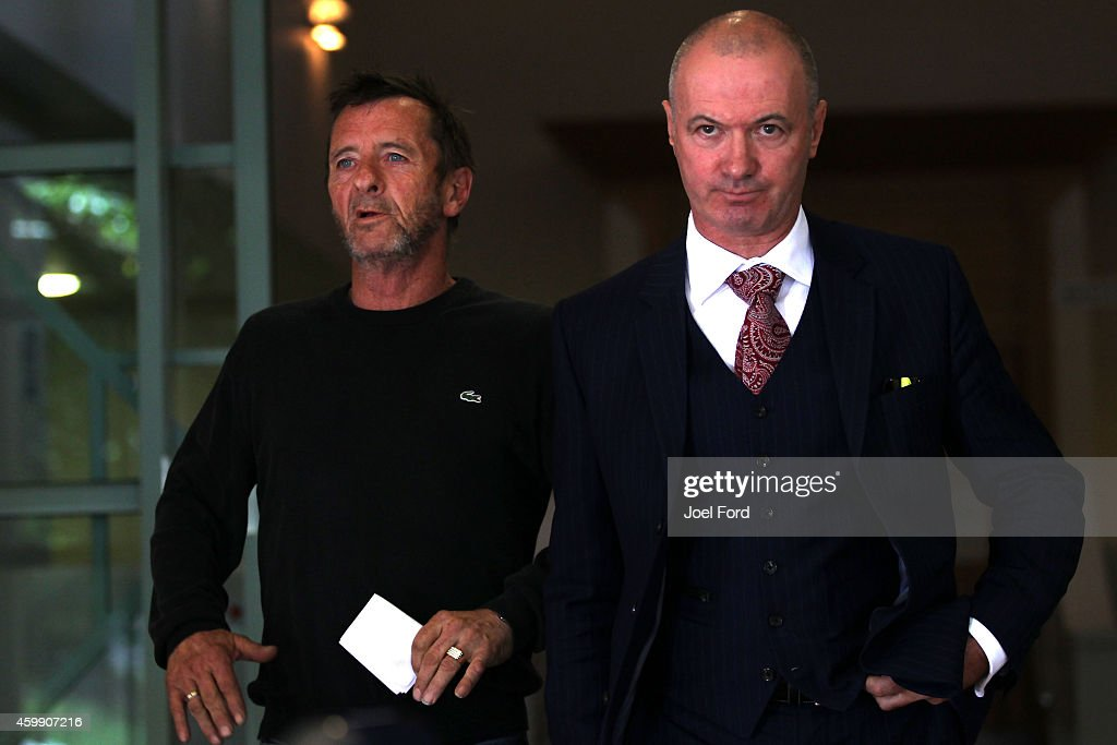 AC/DC drummer Phil Rudd (L) leaves Tauranga District Court with lawyer Craig Tuck after being arrested in relation to breach of bail conditions on December 4, 2014 in Tauranga, New Zealand. Rudd is due back in court on February 10 for a case review hearing for charges of threatening to kill, and possession of cannabis and methamphetamine.
