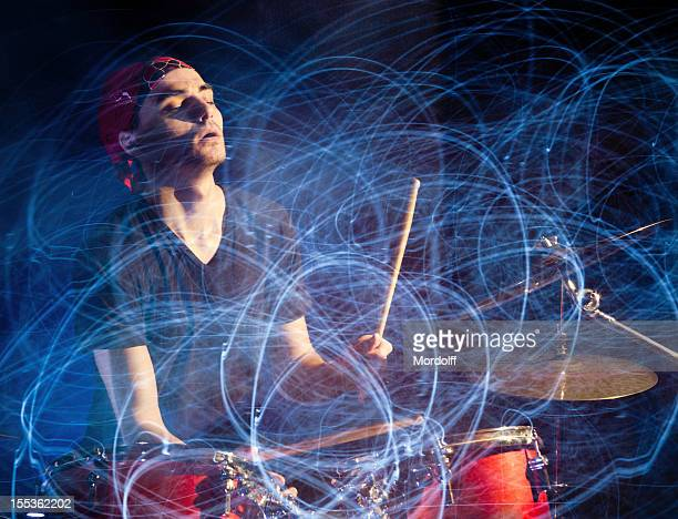 Drummer playing drums in glowing lights