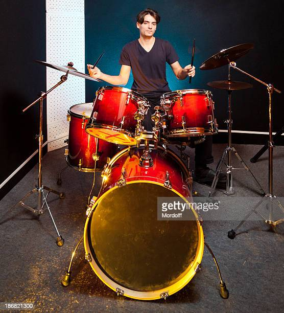Drummer playing drums in music studio