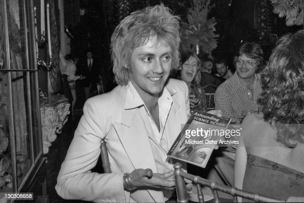 Drummer Roger Taylor of British rock band Queen receives a copy of 'Astounding Science Fiction' during a party thrown by Elektra Records 1977 The...