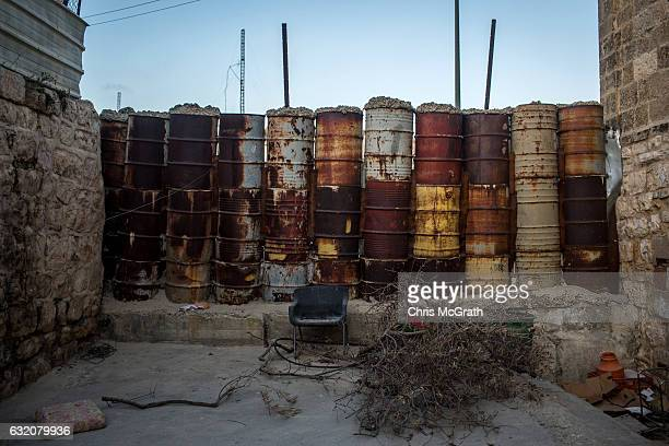 Drums full of soil and sand are seen blocking an entrance to a street that seperates an Israeli settlement and a Palestinian neighbourhood inside the...