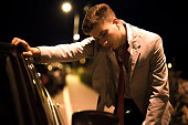 Drunk businessman by the car in night trying to stay awake