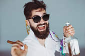 Bearded man with sunglasses holding a bottle of alcohol and cigar at celebration. Ecstatic portrait of drunk man having fun at wild party. Toned colors image