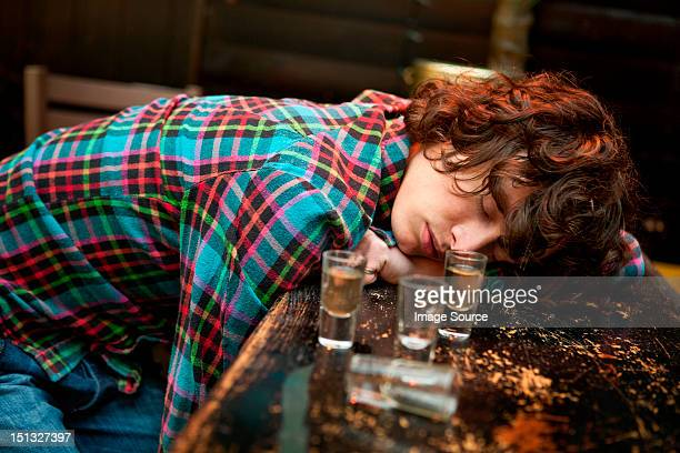 Drunk man slumped on bar asleep
