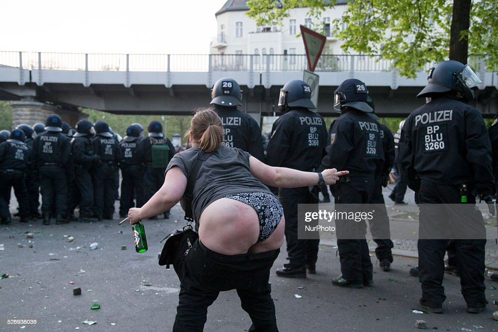 A drunk woman shows her derriere to the police during the clashes occurred between demonstrators and police in the Kreuzberg district on May 1, 2016 in Berlin, Germany. May Day, or International Workers' Day, was established as a public holiday in Germany in 1933. Since 1987 May Day has also become known in Berlin for violent clashes between police and mostly left-wing demonstrators.