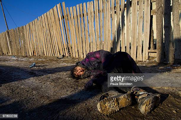 A drunk woman who fell and hit her head is left without any help passed out along the street on March 16 2010 in Ulaan Baatar Mongolia Mongolia...