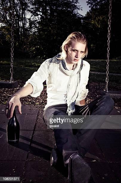 Ivre de jeune homme assis sur le terrain de jeu