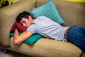 Three Quarter Shot of a Drunk Young Man Sleeping on the Couch in the Home Living Room.