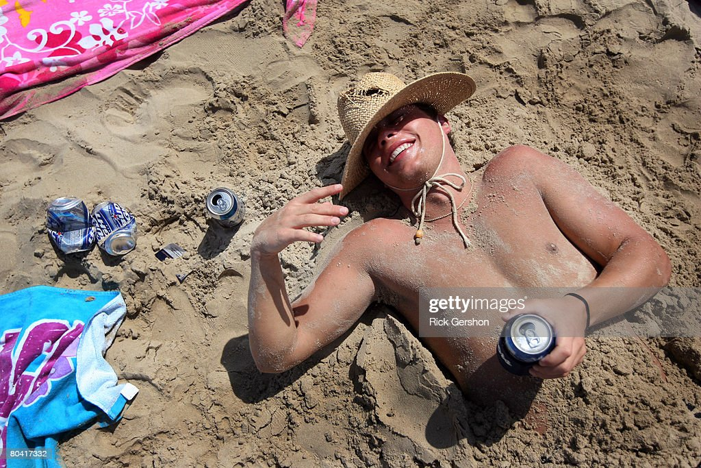 A drunken student lies half buried in sand on the beach during the annual ritual of Spring Break March 25 2008 on South Padre Island Texas The South...