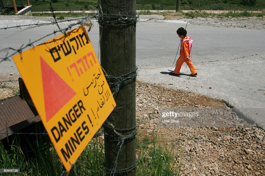 A Druze child passes an Israeli army sign warning of a minefield on her way home from school on April 29 2008 in Majdal Shams in the Golan Heights...