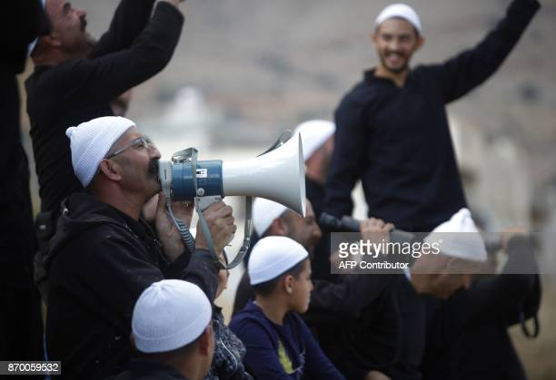 Druze men residing in Majdal Shams in the Israelioccupied sector of the Golan Heights hold their community's flag and use a megaphone to speak to...