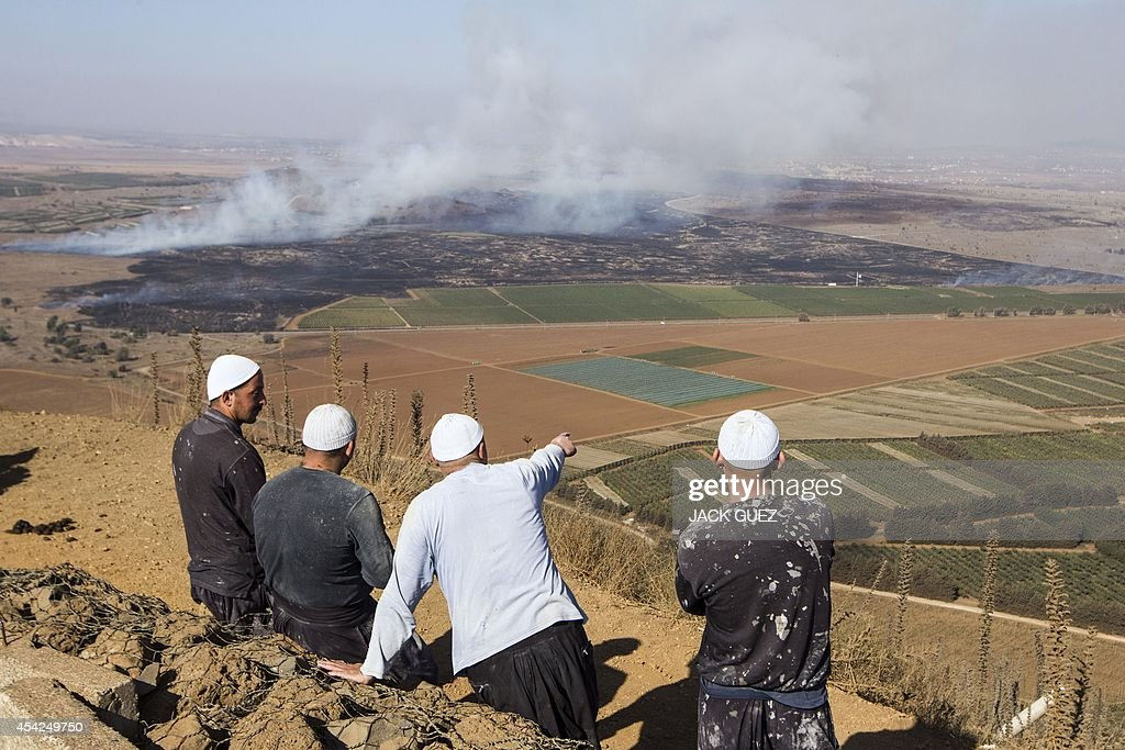 Druze men stand in the Israeliannexed Golan Heights as they look at smoke rising in the distance caused by fighting between forces loyal to Syrian...