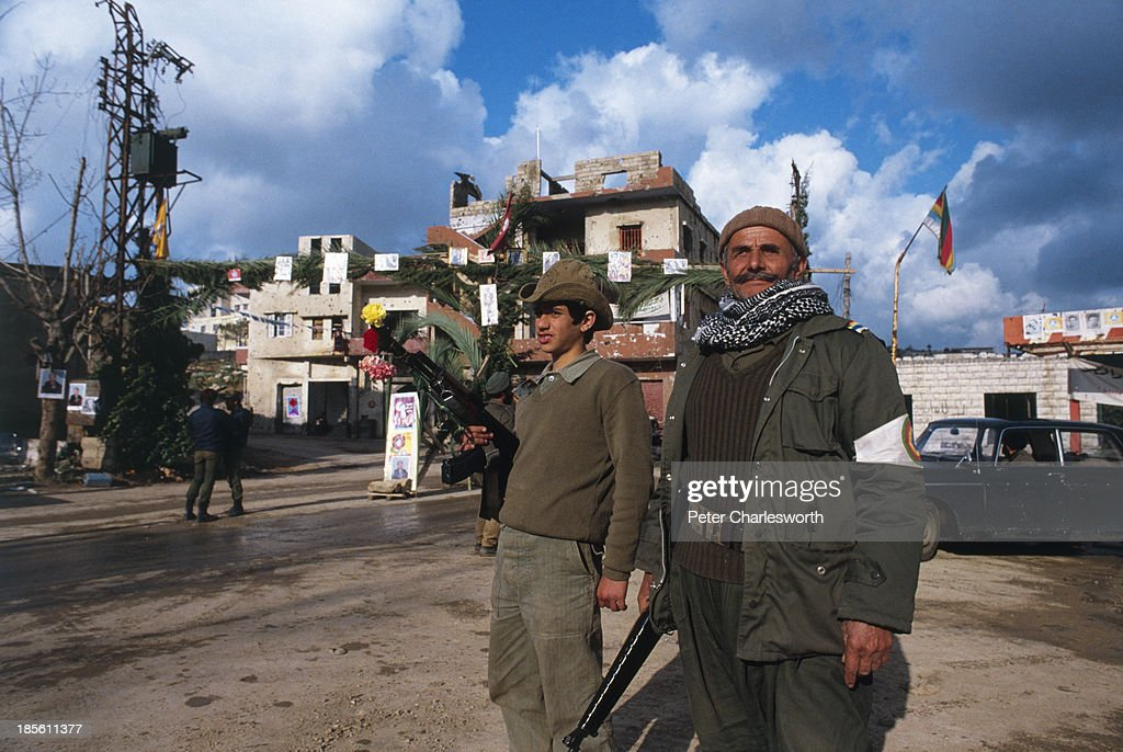 Druze militiamen with flowers in their AK 47 semi automatic rifles stand at a checkpoint in Kabreshmoun a mountain village close to Beirut
