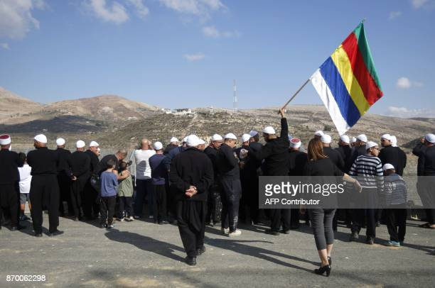 Druze people residing in Majdal Shams in the Israelioccupied sector of the Golan Heights hold their community's flag and use a megaphone to speak to...