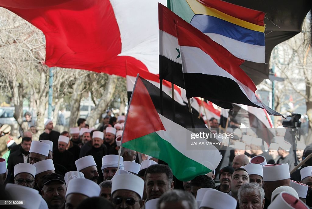 Druze residents of the Buqata village in the Israeli annexed Golan Heights wave a Palestinian flag (front), a Syrian flag (C), and a Druze's community flag during a protest on February 14, 2016 against Israel's annexation of the Golan Heights in 1981. / AFP / JALAA MAREY