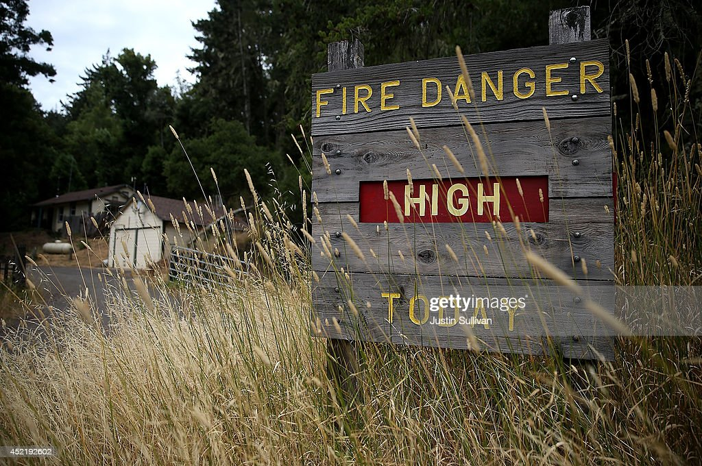 Dry grasses partially cover a fire danger sign that is posted in Samuel P. Taylor state park on July 15, 2014 in Lagunitas, California. As the severe drought in California contiues to worsen, the State's landscape and many resident's lawns are turning brown due to lack of rain and the discontinuation of watering.