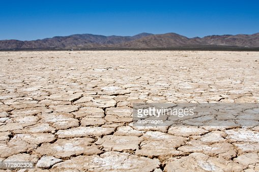 A dry lakebed landscape in front of mountains under blue sky