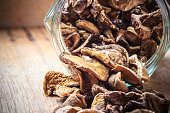 Food. Closeup dry mushrooms spilling out from storage jar on wooden surface table background.