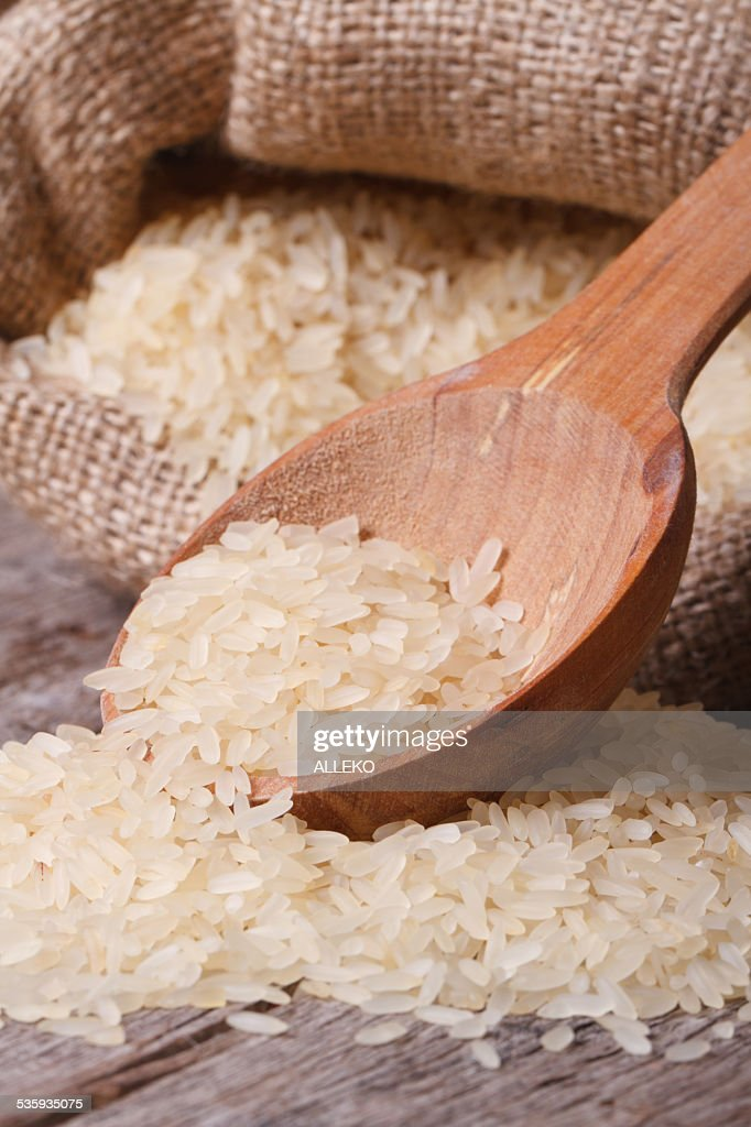 dry rice macro spill out of bag on the table : Stock Photo