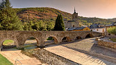 Dry river bed, due to prolonged drought, can be seen under ancient Roman bridge in the picturesque town of Molinaseca, Spain.