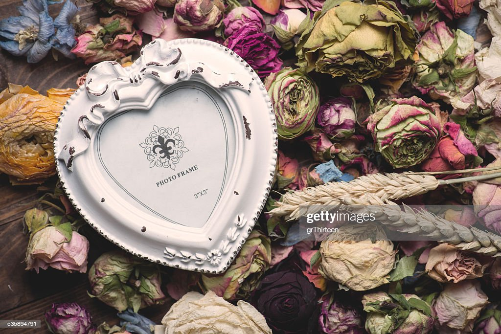 Dry rose flowers heart on wood panel. Valentines background. : Stock Photo