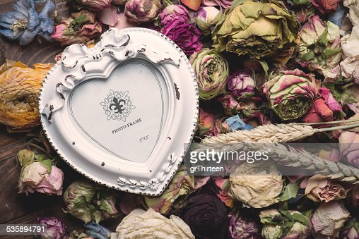 Dry rose flowers heart on wood panel. Valentines background. : Stockfoto