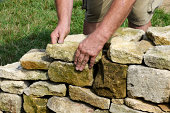 Man building a dry stone wall by hand. These are very popular in England in places like Cumbria, Lake District, Yorkshire, The Dales.