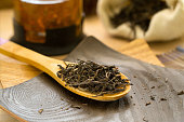Dry tea puerh on a wooden spoon, teapot and a burlap sack of in the background.