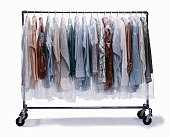 Dry-cleaned clothes wrapped in plastic hanging on clothes rack