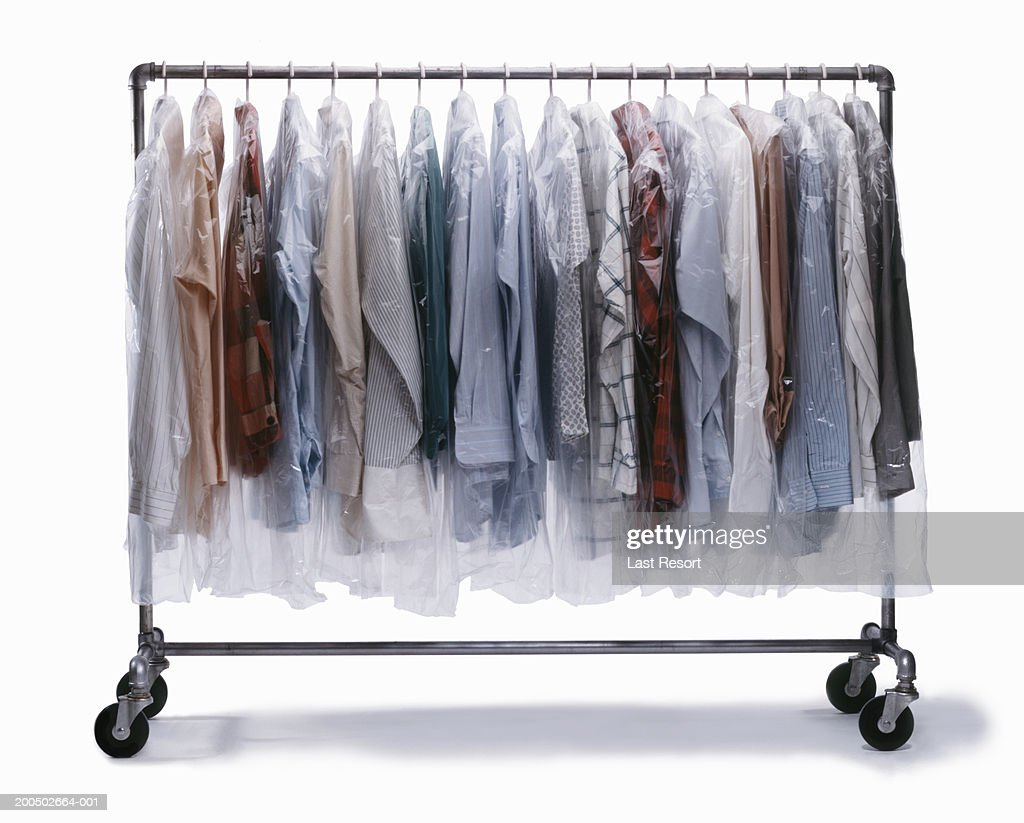 drycleaned clothes wrapped in plastic hanging on clothes rack stock photo