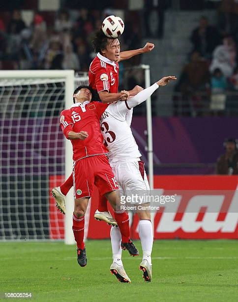 Du Wei of China gets over the top of teammate Yu Tao and Sebastian Suria of Qatar to head the ball during the AFC Asian Cup Group A match between...