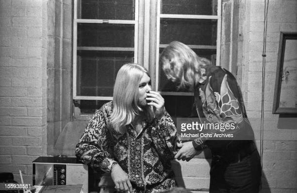 Duane Allman chats with his brother Greg Allman backstage before the Allman Brothers' performance at the Sitar on October 17 1970 in Spartanburg...