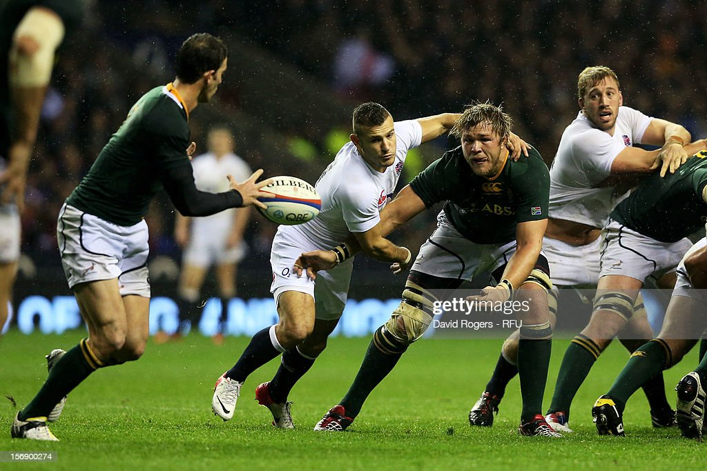 Duane Vermeulen of South Africa passes the ball under pressure from Danny Care of England during the QBE International match between England and South Africa at Twickenham Stadium on November 24, 2012 in London, England.