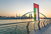 Dubai Downtown skyline with UAE national flag over the water canal at sunrise. Dubai, UAE.